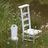 Photograph of two white chairs in a field