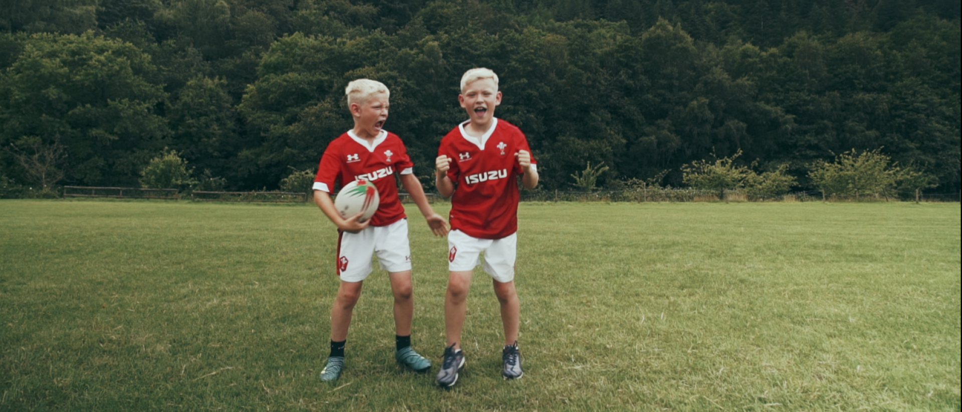 Two young boys playing rugby in Welsh kits
