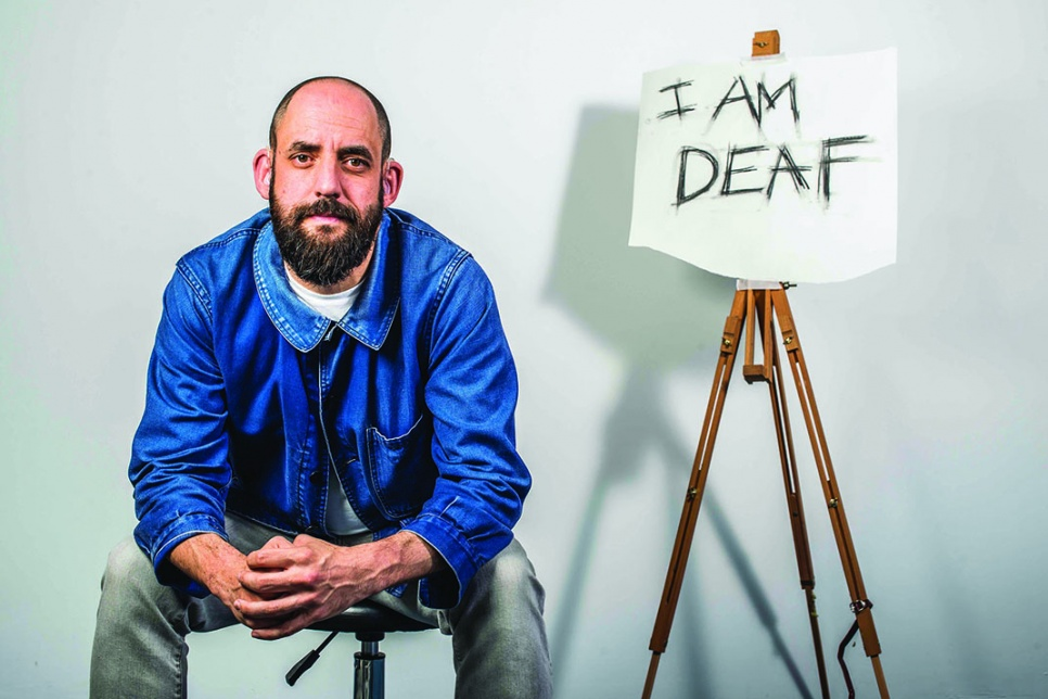 Actor sits on a stool beside a poster that reads 'I am deaf'
