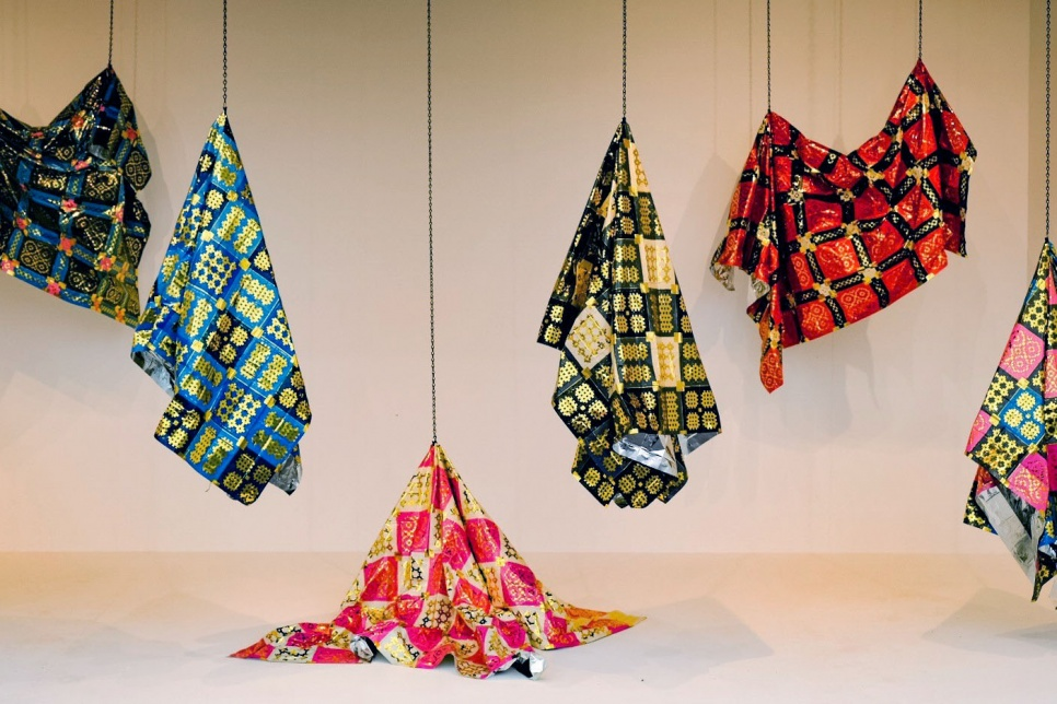 Image of multiple welsh quilts made from emergency blankets hanging from the ceiling