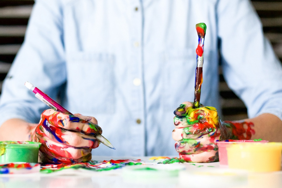 Man holding paintbrushes covered in paint
