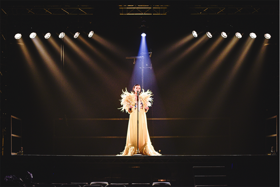 Lady stood centre stage in a spotlight, dressed in long, white, feathered gown