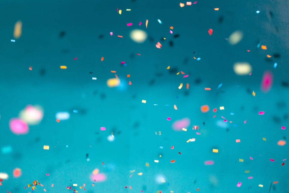 Blue background showing multicoloured confetti falling