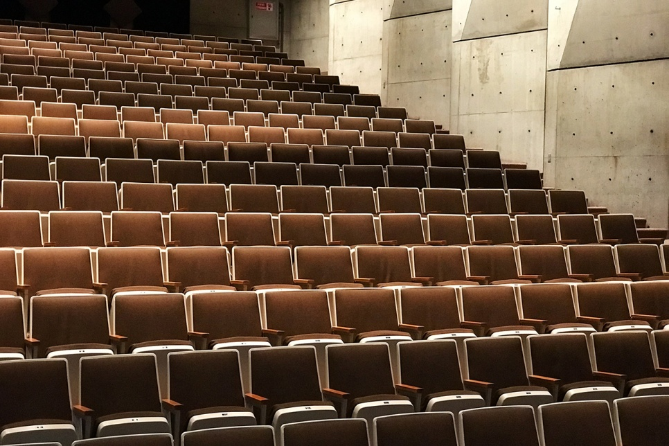 Rows of empty theatre chairs