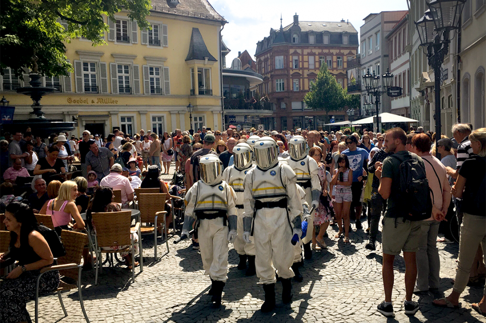 Astronauts walking through crowds in a picturesque German town