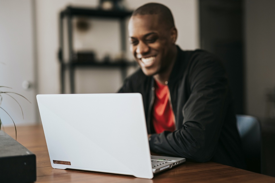 Man smiles at laptop