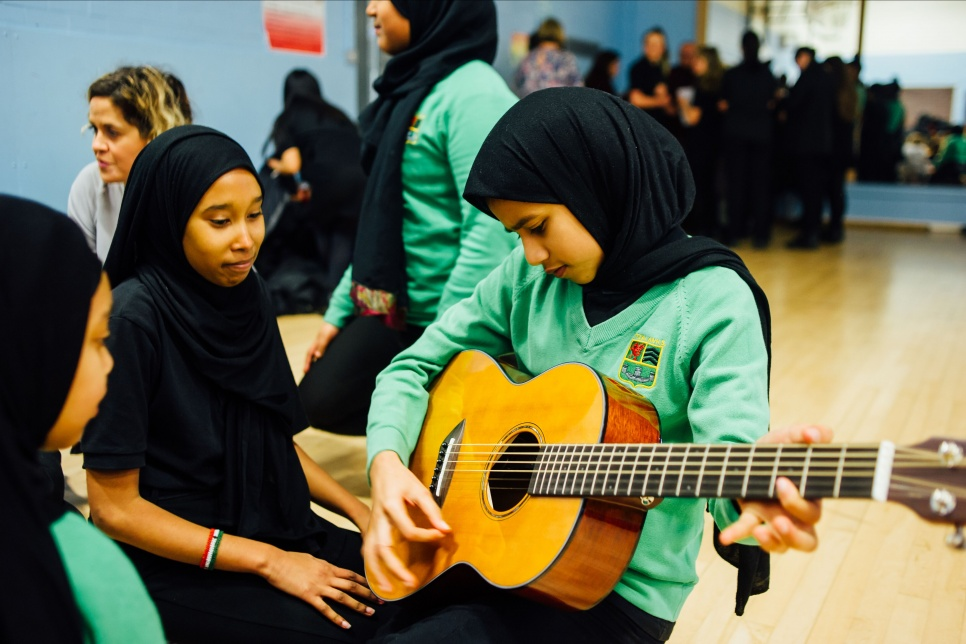 Three pupils from Fitzalan High School Cardiff, with one pupil playing a guitar