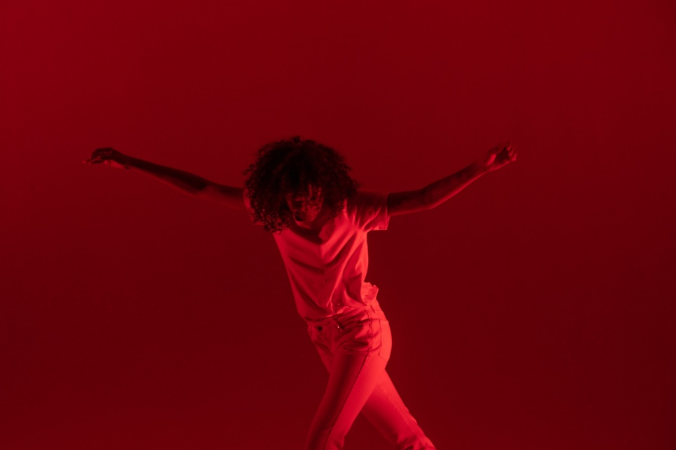 A person with arms stretched out dancing with red lighting as background