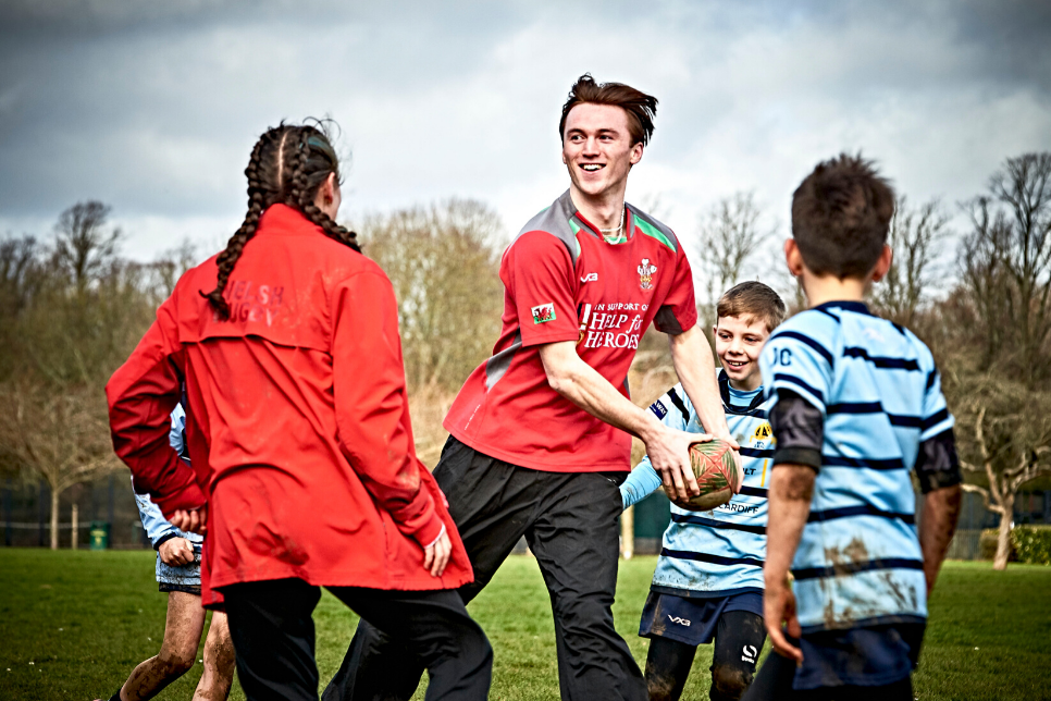 A dancer holding a rugby ball with 3 young rugby players around him