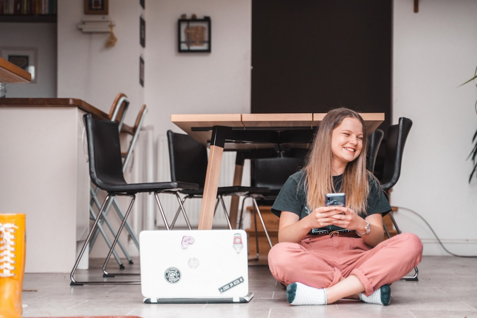 Young girl sits cross legged holding her smartphone
