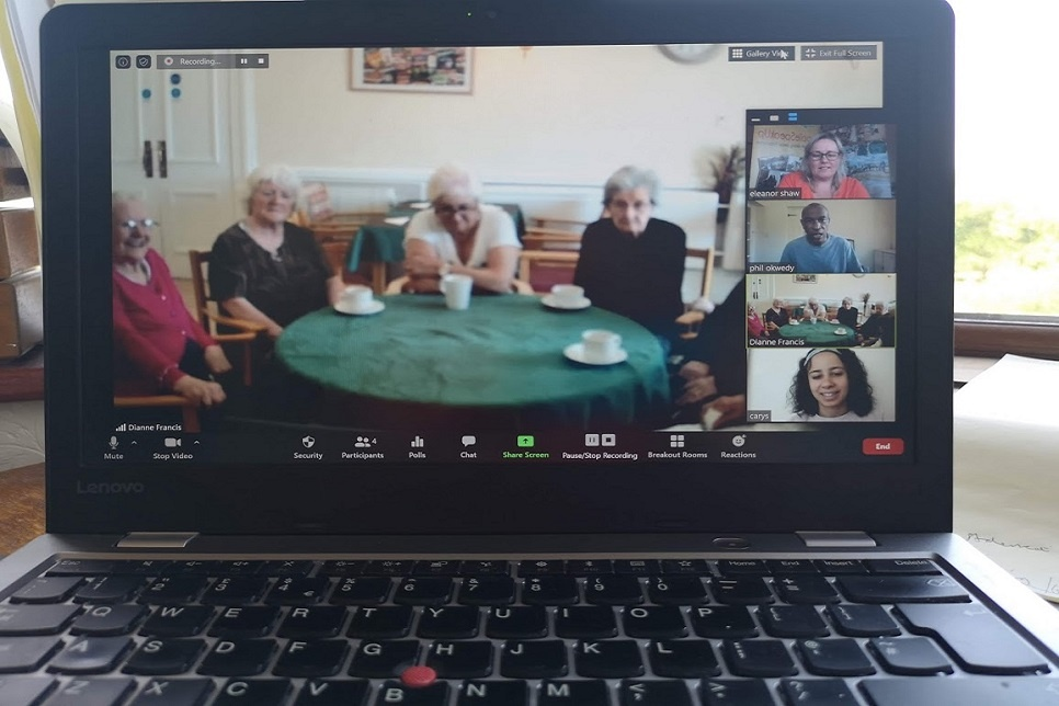 Computer screen showing people sitting around a table
