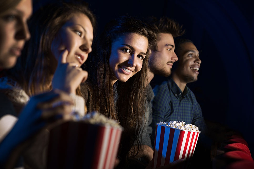 image of people in a theatre with popcorn